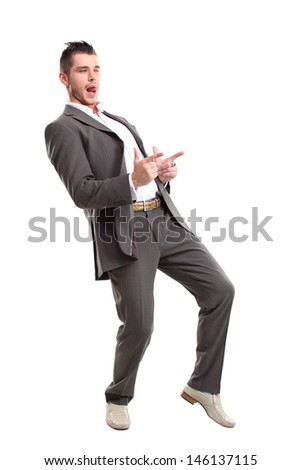Young surprised business man pointing at something interesting on a white background