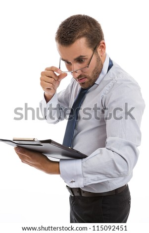 Young surprised businessman looking over eyeglasses at black folder with documents, over white background. - stock photo
