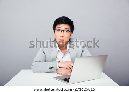 Young surprised businessman sitting at the table with laptop over gray background and looking at camera