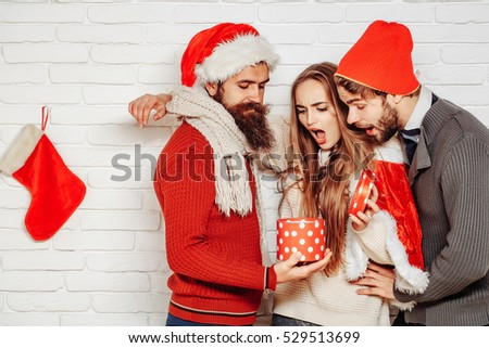 Young surprised Christmas or new year people friends of bearded men with open gift box and pretty sexy girl or beautiful woman in red santa claus xmas costume with sock on white brick wall