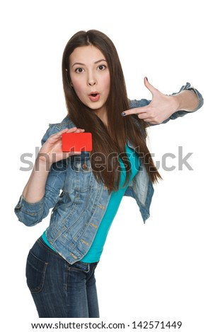 Young surprised female holding blank credit card and pointing at it against white background - stock photo