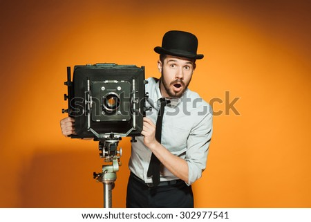 Young surprised man in hat as photographer with retro camera on an orange background - stock photo