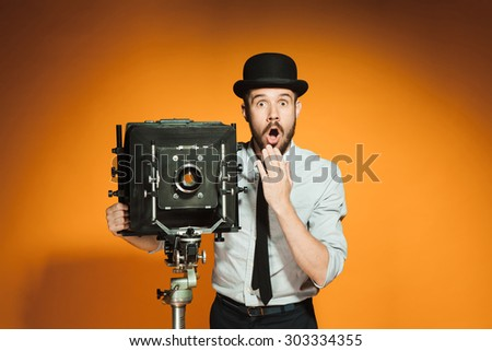 Young surprised man in hat as photographer with retro camera on an orange background
