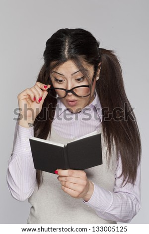 Young surprised nerd woman studying on white background - stock photo