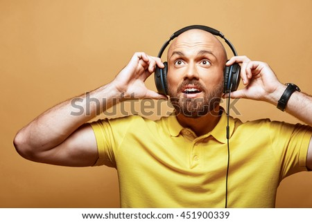 Young surprised sexy bald bearded man with earphones on yellow background  - stock photo
