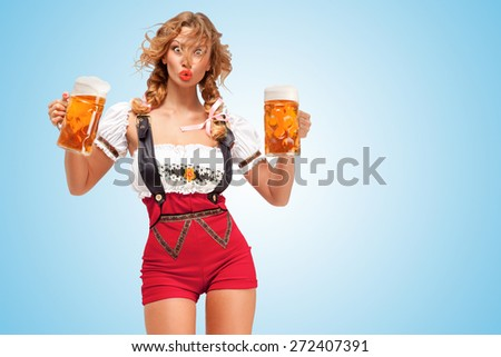 Young surprised sexy Swiss woman wearing red jumper shorts with suspenders in a form of a traditional dirndl, holding two beer mugs on blue background. - stock photo