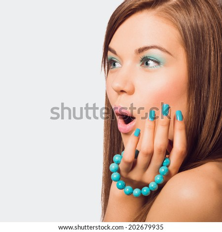 Young surprised woman holding a turquoise bracelet with bright manicure. - stock photo