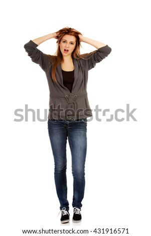 Young surprised woman holding hands inside hair - stock photo