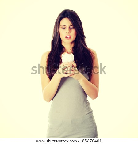 Young surprised woman with lot of cugar in glass. Lot of callories in drink - stock photo