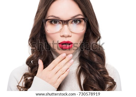 Young surprised woman with red lipstick wearing trendy glasses and looking at camera, isolated on white