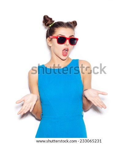 Young Surprised Woman with sunglasses looking at camera. Beauty girl with bright makeup hairstyle with horns in a blue dress having fun. On a white background, not isolated - stock photo