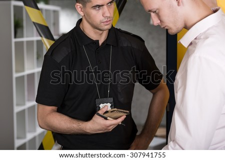 Young suspected man talking with police officer - stock photo