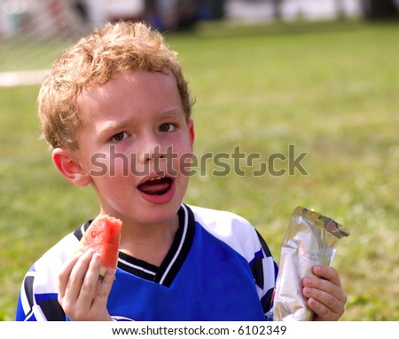 Young sweaty boy having halftime snack of watermelon and juice - stock photo