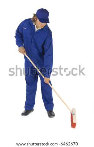Young sweeping man in blue workwear. Isolated on white background