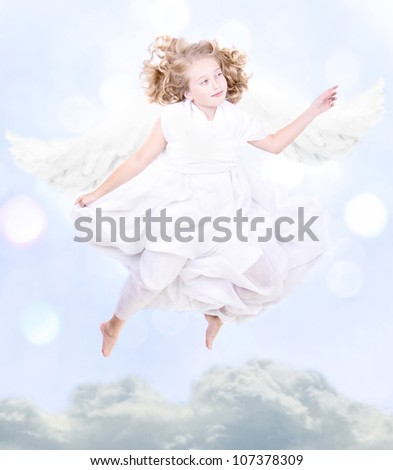 Young sweet angel flying above the clouds - stock photo