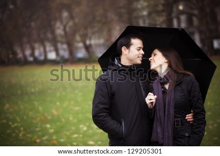 Young sweet couple sharing umbrella and smiling each other - stock photo