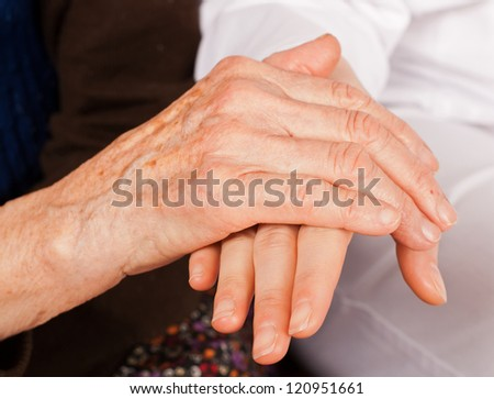 Young sweet doctor holds the old woman hands - stock photo