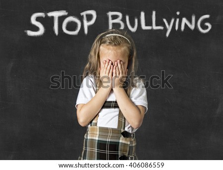 young sweet junior schoolgirl victim of bully crying sad standing in front of school class blackboard with chalk text stop bullying in school children bullied and education stress - stock photo