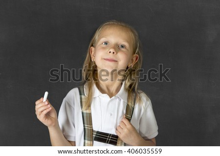 young sweet junior schoolgirl with blonde hair standing and smiling happy  isolated in blackboard background holding chalk wearing school uniform in children education success and fun - stock photo