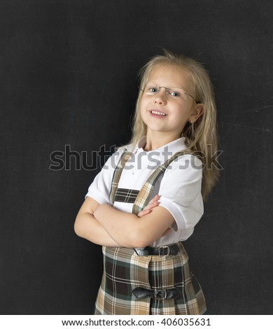 young sweet junior schoolgirl with blonde hair standing and smiling happy  isolated in blackboard background wearing school uniform in children education success and fun - stock photo