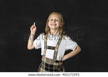young sweet junior schoolgirl with blonde hair standing happy and smiling isolated in front of classroom blackboard holding chalk wearing school uniform in children education success and fun - stock photo