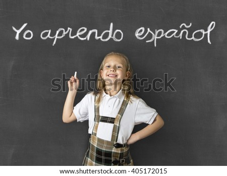 young sweet junior schoolgirl with blonde hair standing happy and smiling isolated in front of classroom blackboard holding chalk in children learning spanish language and education concept - stock photo