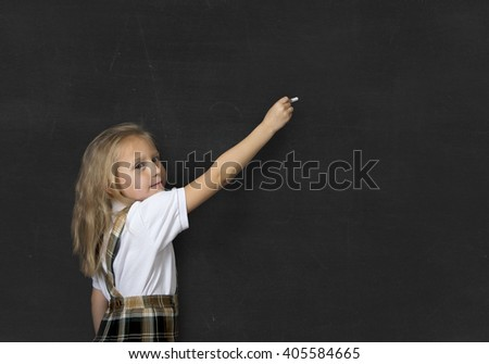 young sweet junior schoolgirl with blonde hair standing happy and smiling writing with chalk isolated in front of school classroom blackboard wearing school uniform in children education - stock photo