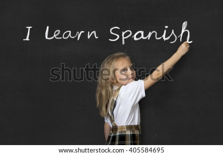 young sweet junior schoolgirl with blonde hair standing happy writing with chalk on class blackboard I learn Spanish text in children learning language and education concept - stock photo