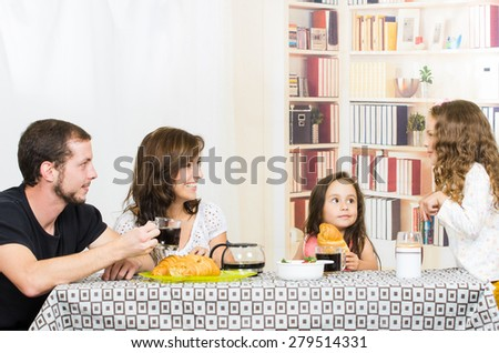 Young sweet parents with two little girls having breakfast in the dining room - stock photo