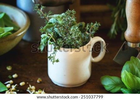 Young sweet peas and mix of herbs rosemary and basil with vintage kitchen utensil over wooden table - stock photo