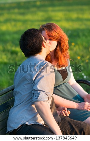 Young sweethearts sitting together on a park bench kissing in evening sunlight