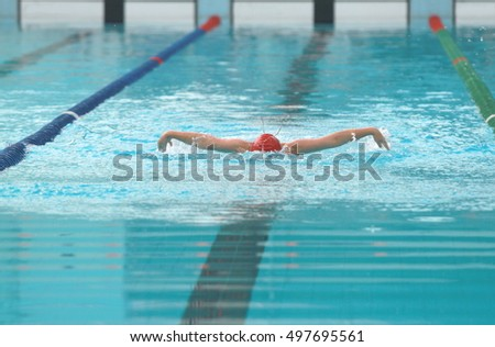 Young swimmer wearing red cap practice butterfly swimming stroke in a swimming pool
