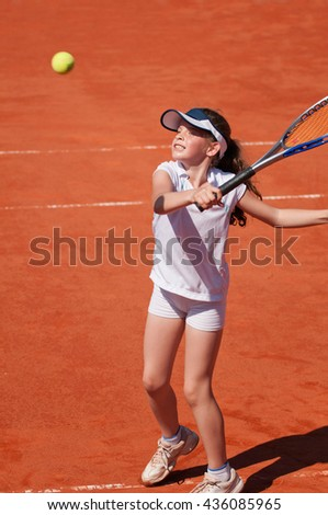 Young talented girl hits a volley on the tennis court - stock photo