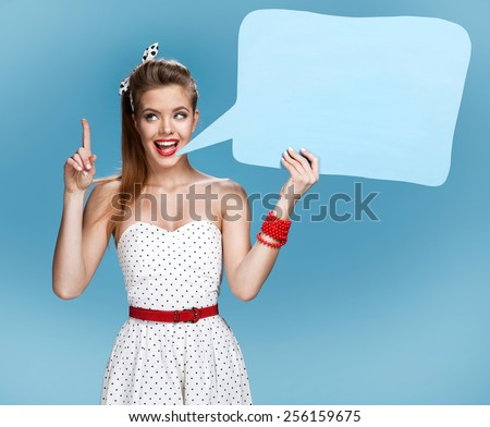 Young talkative woman showing sign speech bubble banner looking happy excited / young American pin-up girl on blue background having idea  - stock photo
