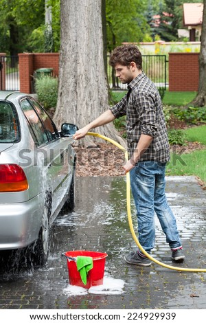 Young tall man spalshing his silver car by garden hose - stock photo