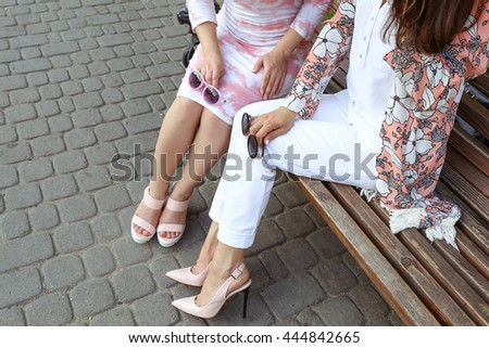 Young tanned beautiful girls in white pants and light floral pink patent in leather high-heeled shoes. Stylish girl with long hair sitting on a bench in the city. Summer outfit, street fashion look