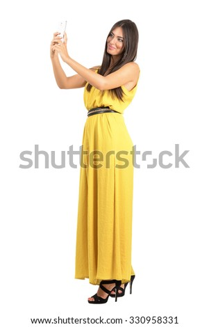 Young tanned beauty in yellow dress taking photo with mobile phone. Full body length portrait isolated over white studio background.  - stock photo