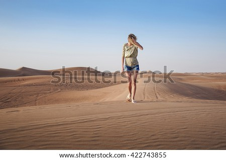 Young tanned girl in denim shorts and a patterned blouse is walking alone on the sand dunes of the desert - stock photo