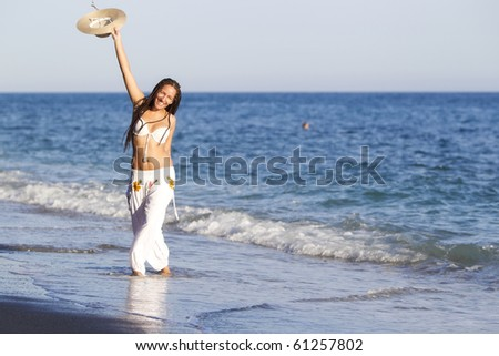 Young tanned girl saluting at the beach - stock photo
