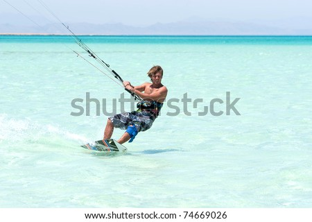young tanned kiter with long hair  kiting in the surrounding of  turquoise sea spray - stock photo
