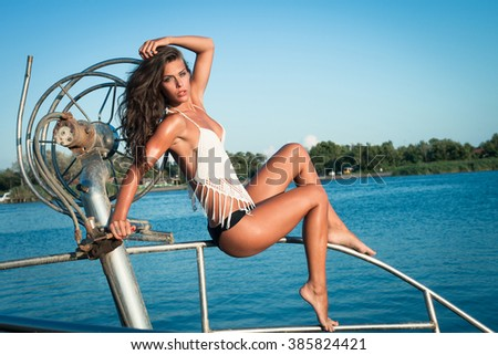 young tanned woman in bikini on old fishing  boat posing full body shot - stock photo