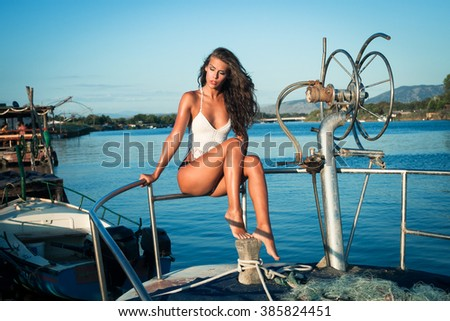 young tanned woman in bikini on old fishing  boat posing full body shot