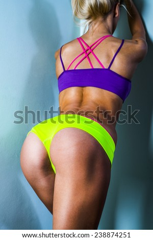 Young tanned woman with beautiful sporty buttocks and slim waistline isolated gray wearing green and pink sexy sporty style shorts over underwear Water drops on elastic brown wet skin No face torso - stock photo