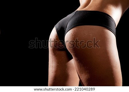 Young tanned woman with beautiful sporty buttocks wearing black sexy sporty style shorts. Water drops on wet skin - stock photo