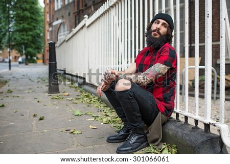 Young tattooed man intimate portrait in Shoreditch borough. London, UK. Hipster style. - stock photo