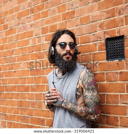 Young tattooed man portrait listening to music against brick wall in Shoreditch borough. London, UK. Hipster style. - stock photo