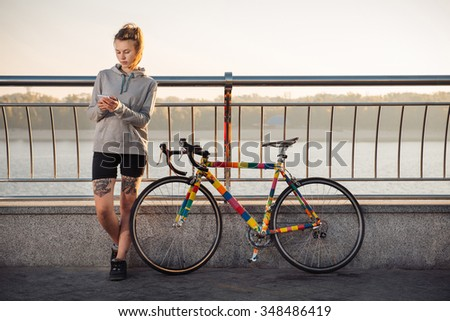 Young tattooed woman standing near bicycle and using smartphone  - stock photo
