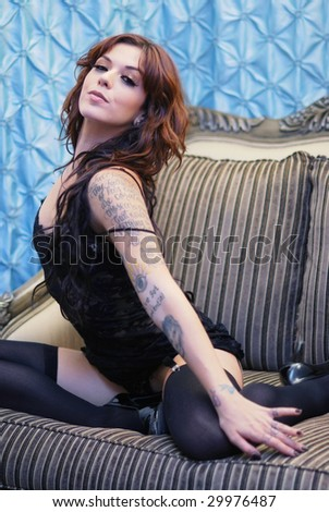Young tattooed woman wearing black lace lingerie on sofa - stock photo