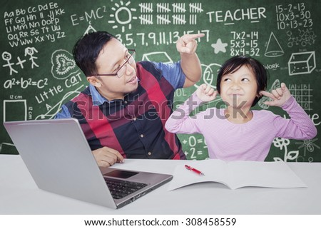 Young teacher advising his female student to study in the classroom with a book and laptop - stock photo