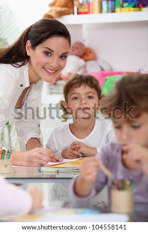 Young teacher and children in a classroom - stock photo